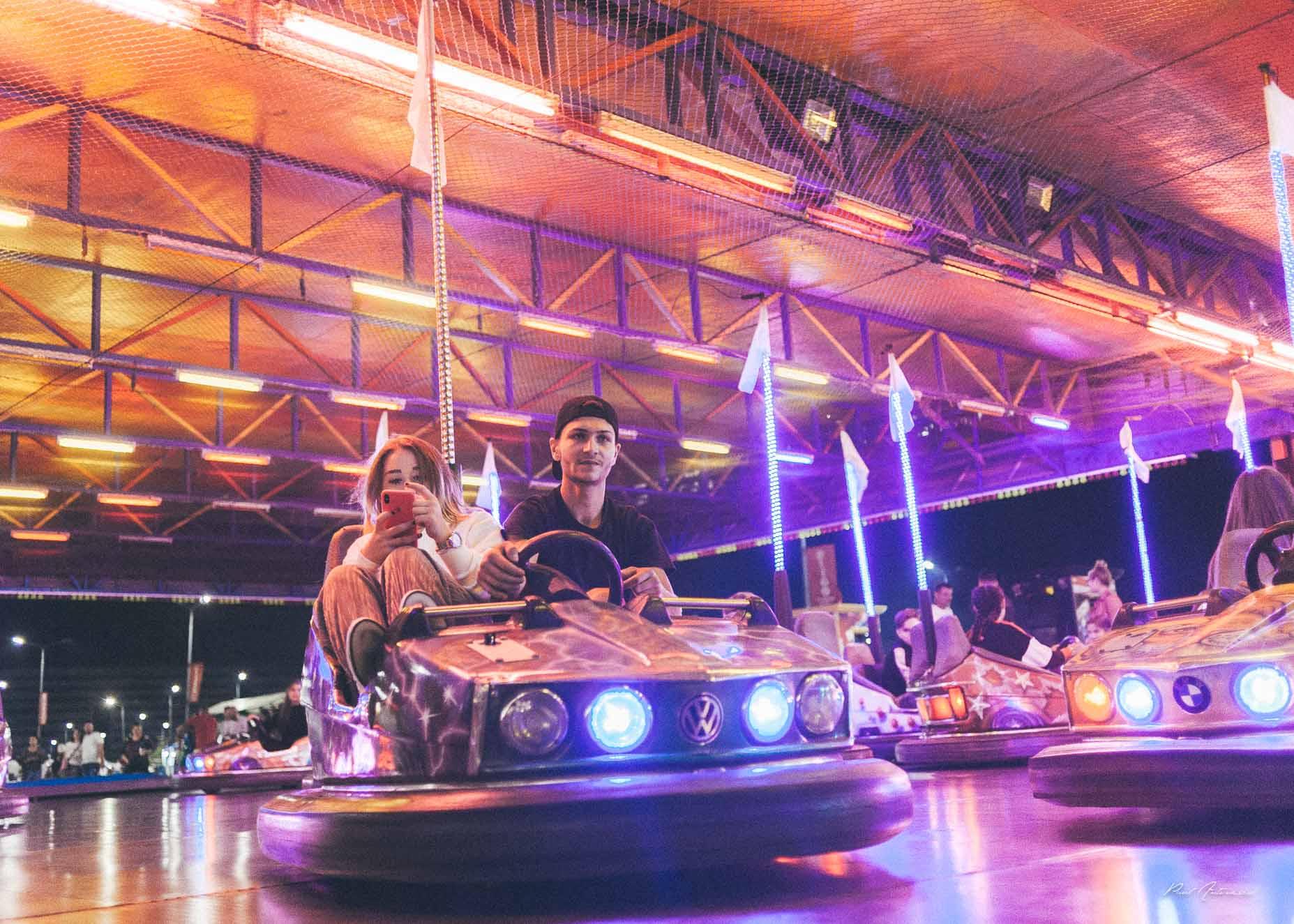 Oameni in parcul de distractie, la masinute in oraselul copiilor.