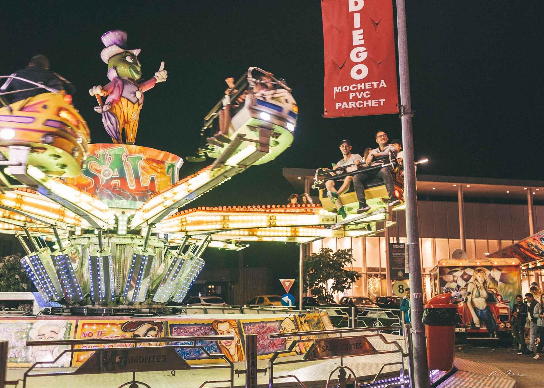Oameni in parcul de distractie, la tiribombe in oraselul copiilor.