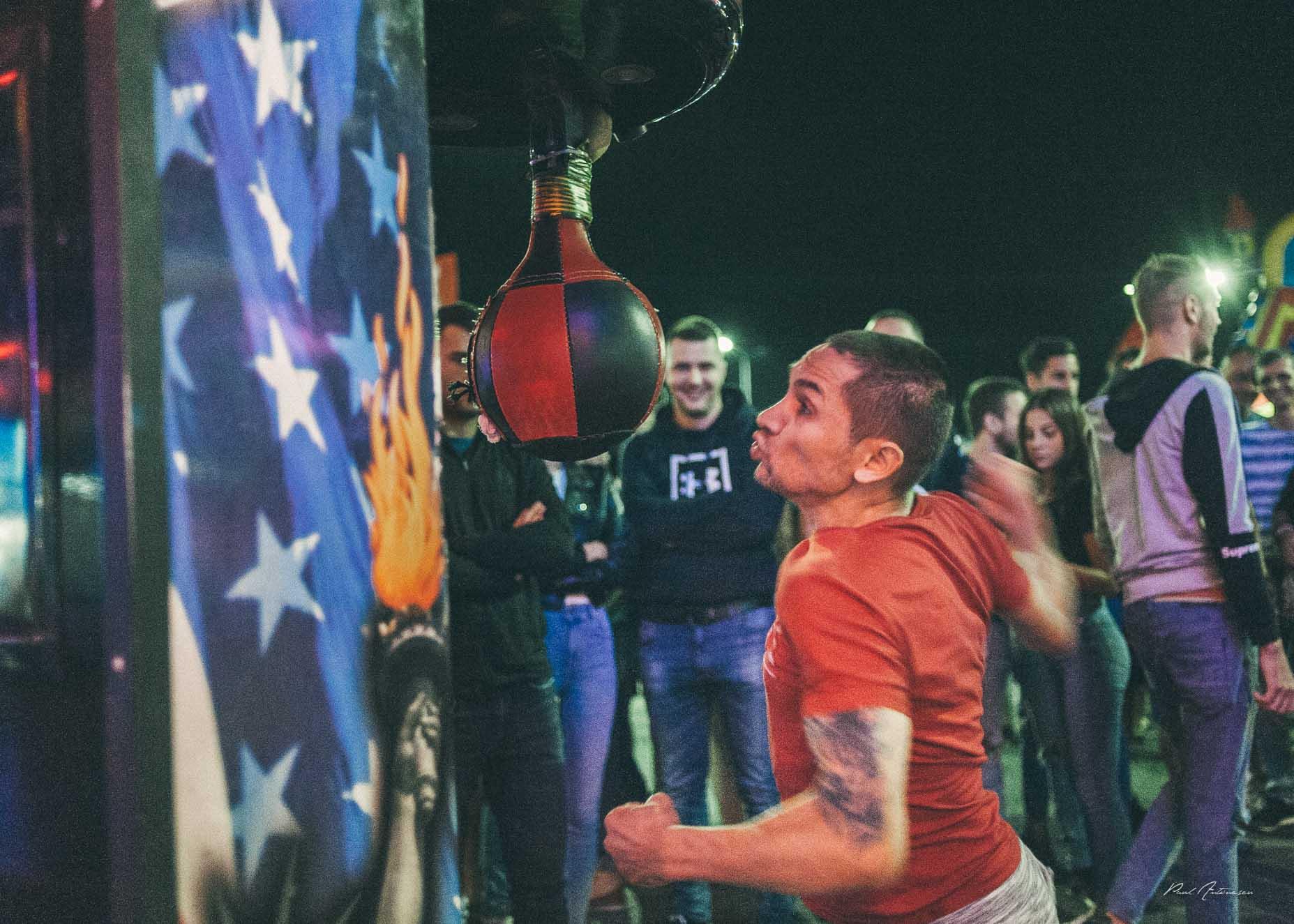 Tanar lovind un sac de box in parcul de distractii, oaraselul copiilor