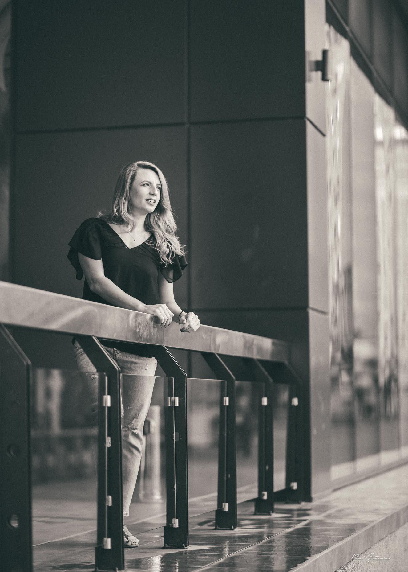 Potret alb negru de fata cu par blond ce poarta blugi, sandale negre, bluza neagra, fotografiata urban pe timp de zi