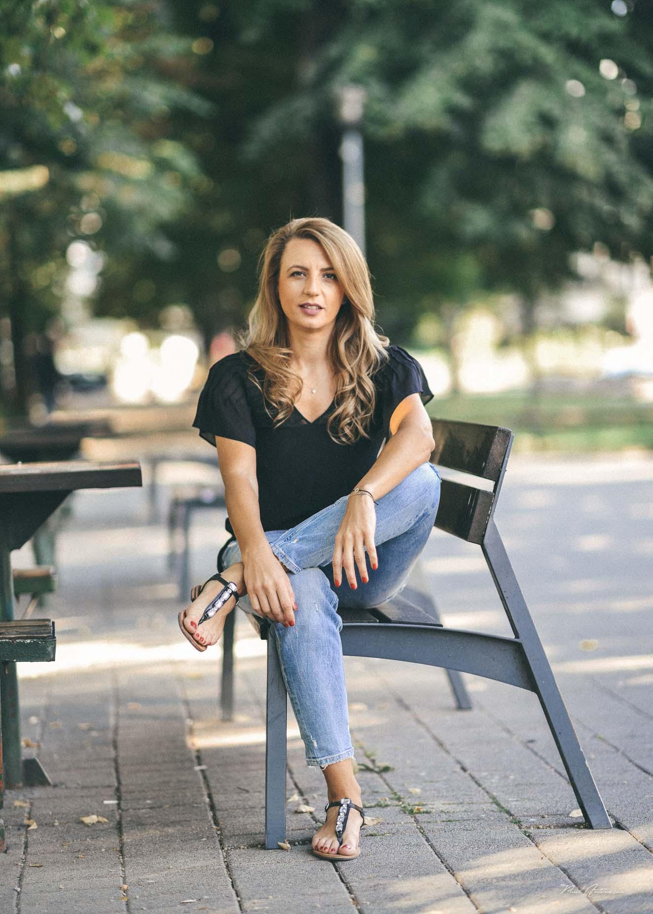 Potret de fata cu par blond ce poarta blugi, sandale negre, bluza neagra, fotografiata urban pe timp de zi