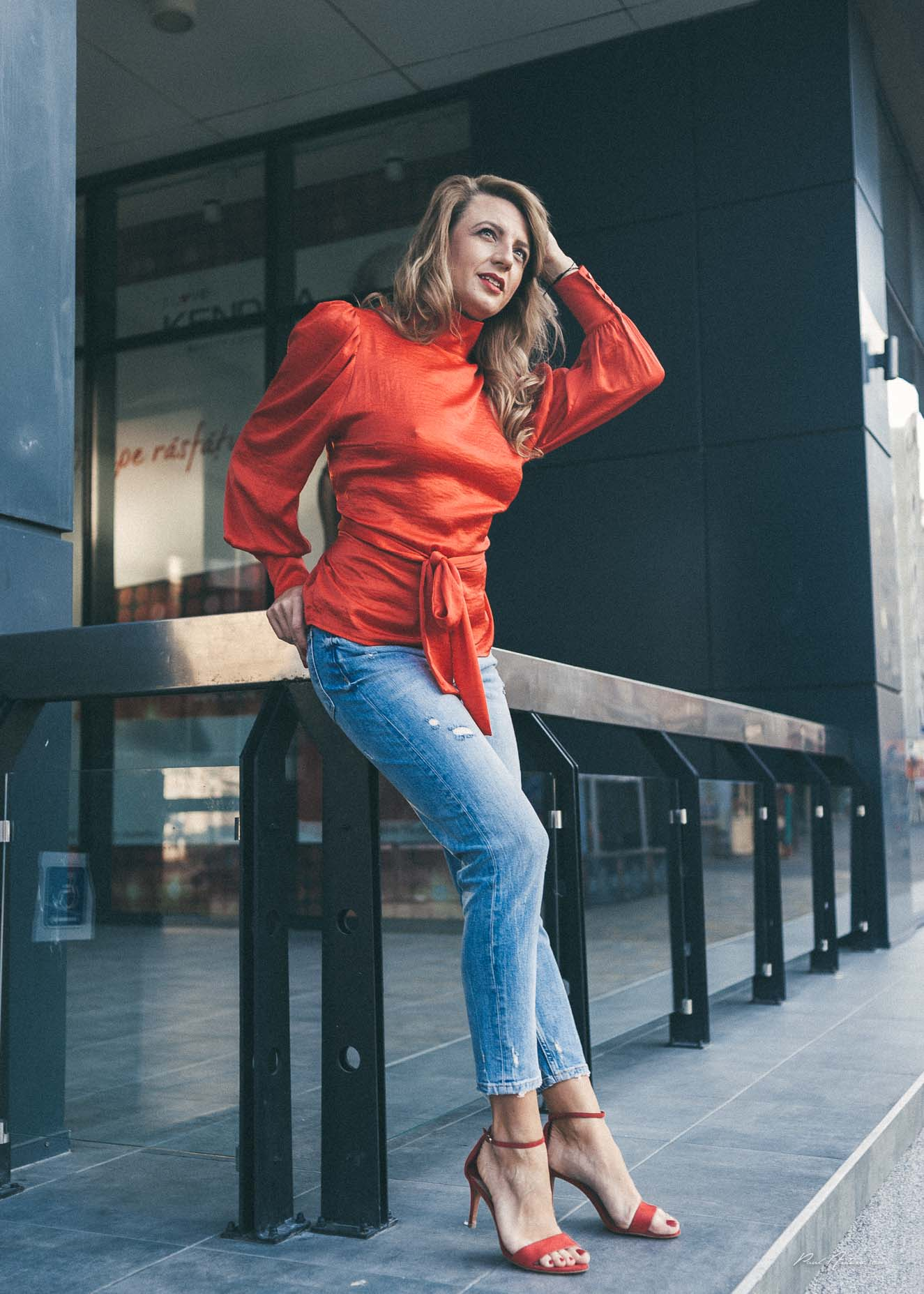 A pretty blonde girl wearing blue jeans, red fancy shoes and a red top posing for the camera in the city.