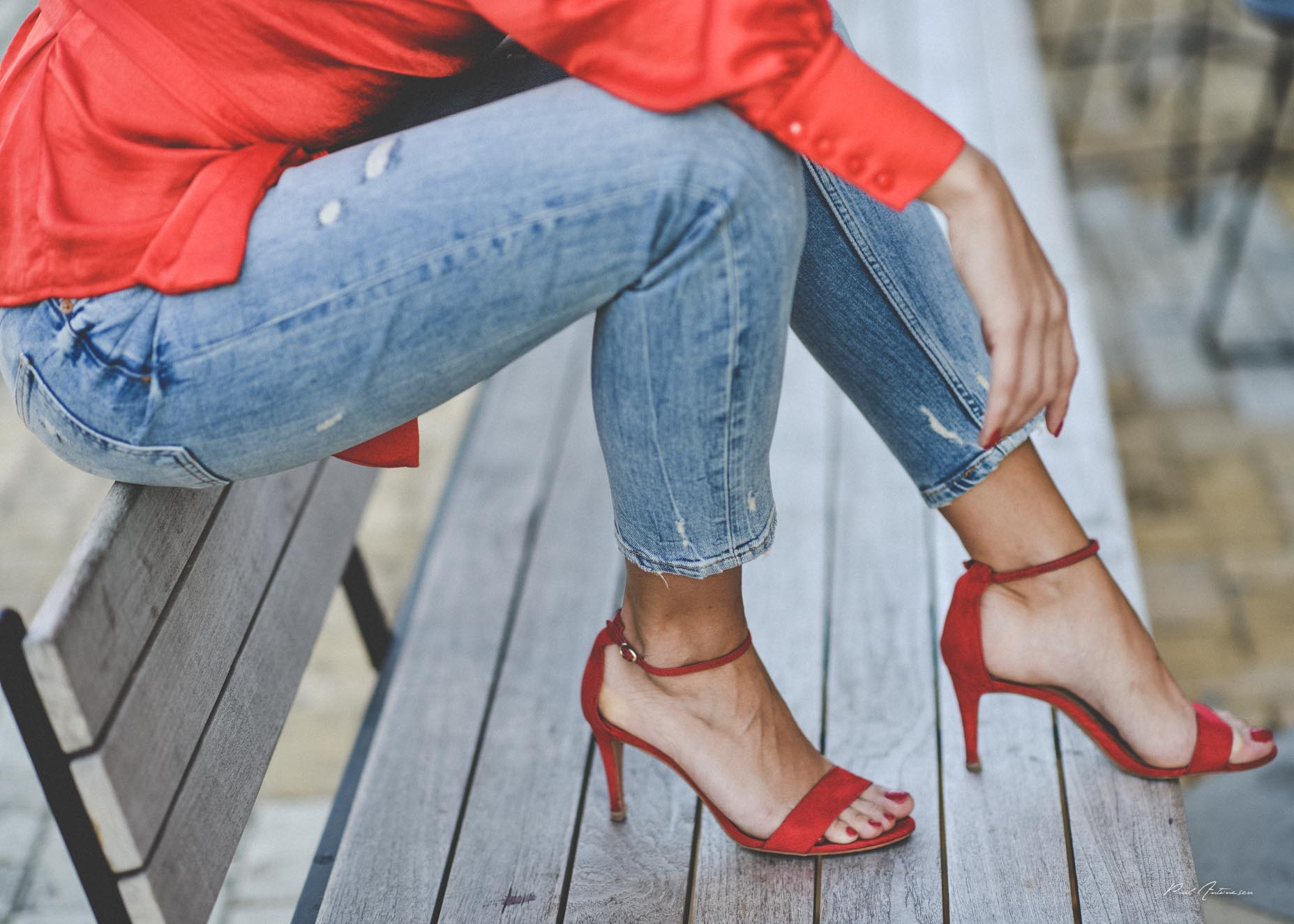 Details of a pretty blonde girl wearing blue jeans, red fancy shoes and a red top posing for the camera in the city.