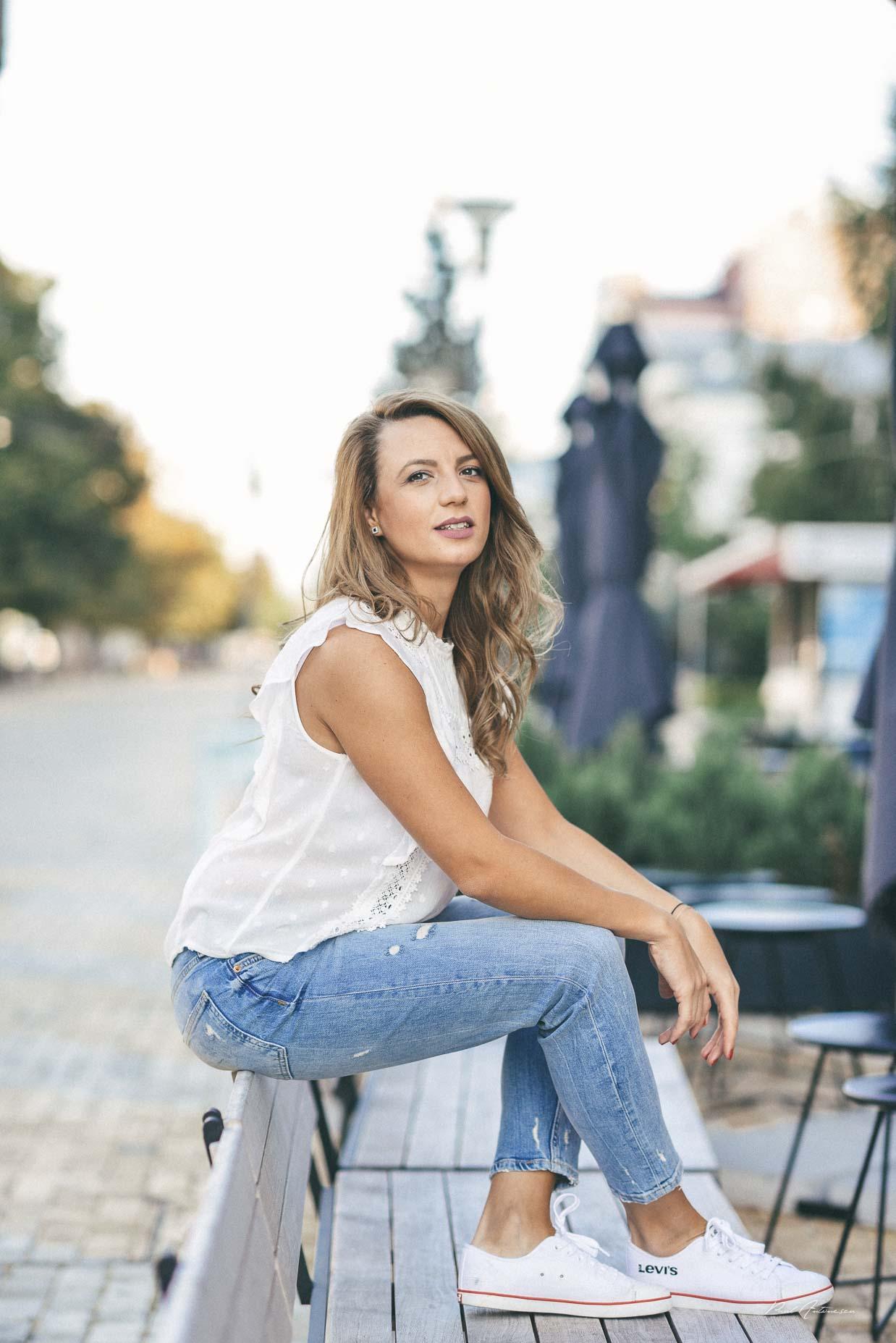 Potret de fata cu par blond ce poarta blugi, tenisi albi, bluza alba, fotografiata urban pe timp de zi