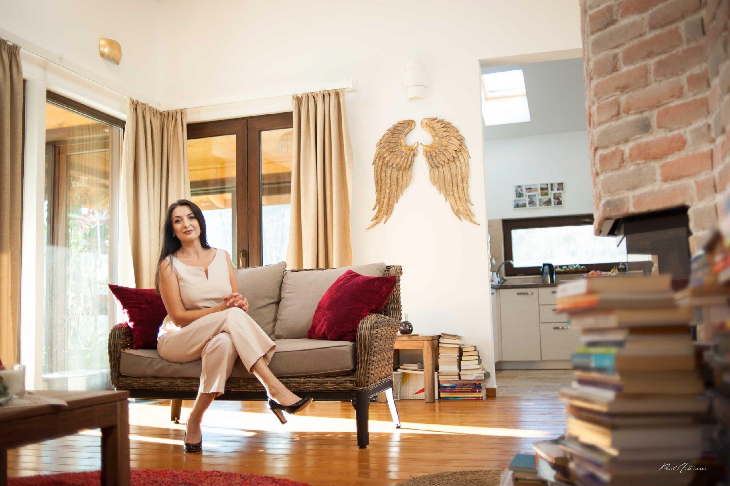O doamna eleganta, cu par lung, negru, imbracata in culori deschise, fotografiata in casa, pe o canapea, cu lumina naturala.