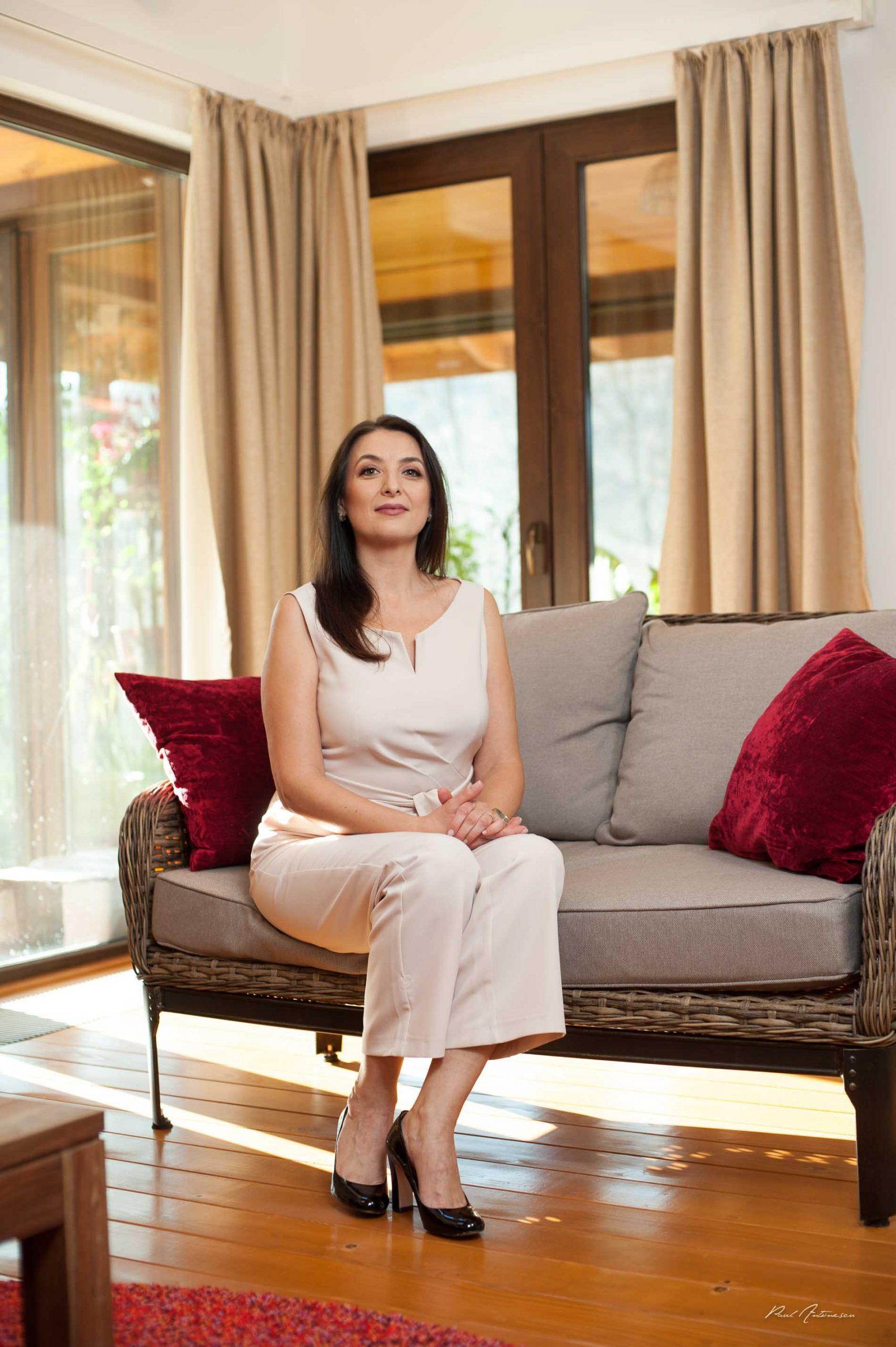 Doamna fotografiata minimalist, razand, cu par lung, negru, la lumina naturala, pe canapea, in casa.
