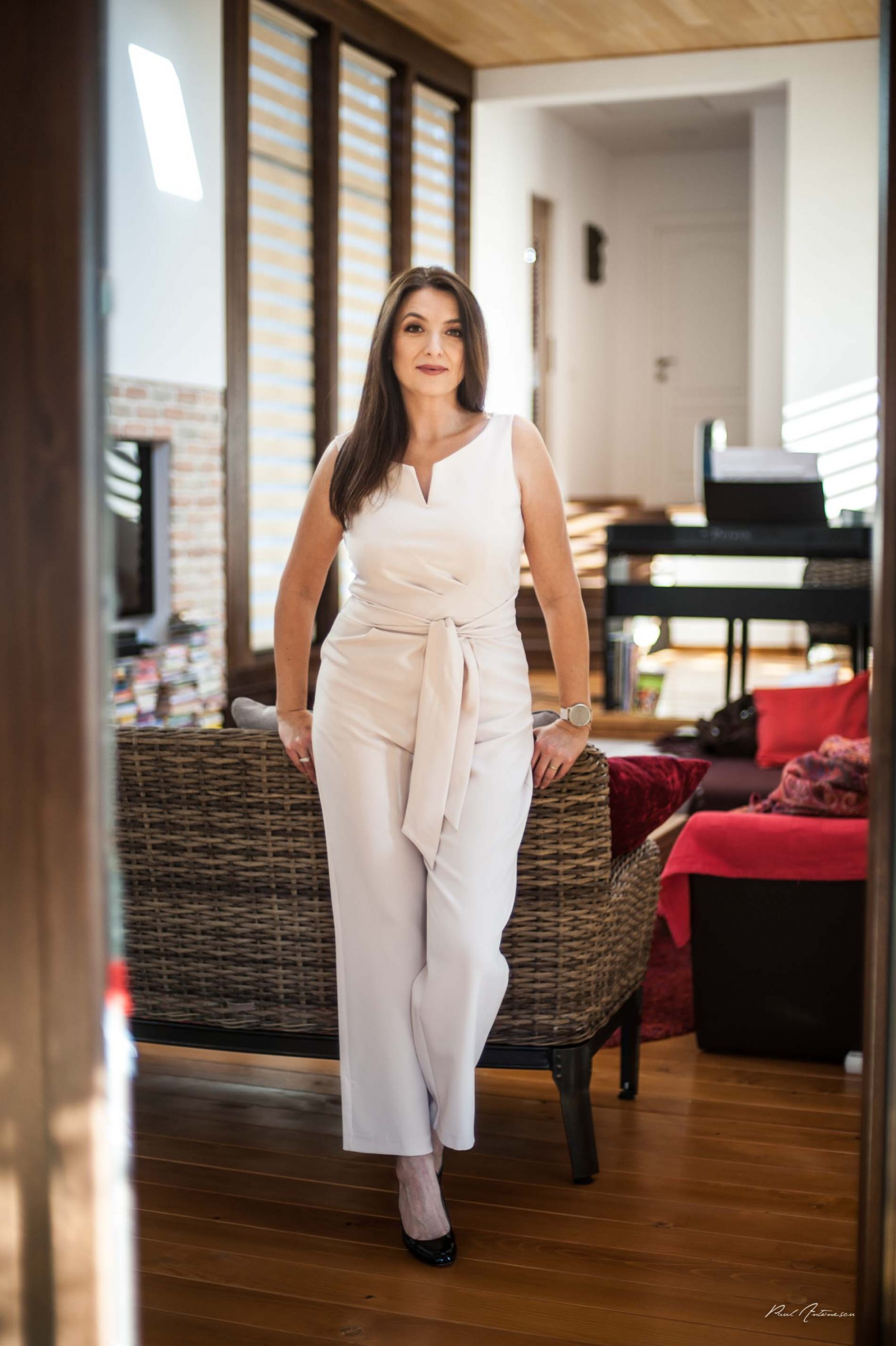 Doamna fotografiata minimalist, razand, cu par lung, negru, la lumina naturala, in picioare, in casa.