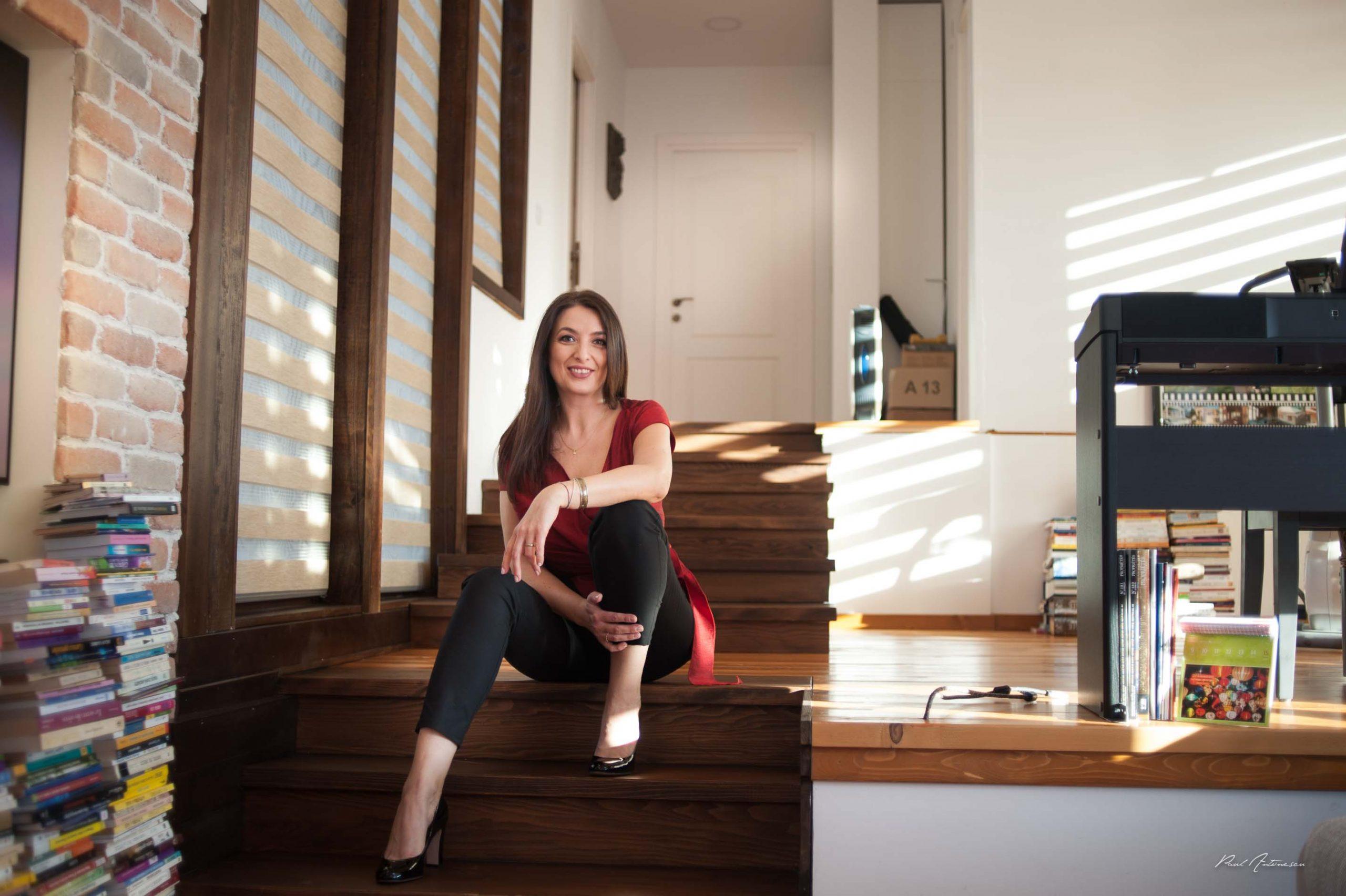 Doamna fotografiata minimalist, razand, cu par lung, negru, la lumina naturala, pe trepte, in casa.